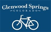 Bike Glenwood Springs Logo featuring white bicycle and writing on a dark blue background